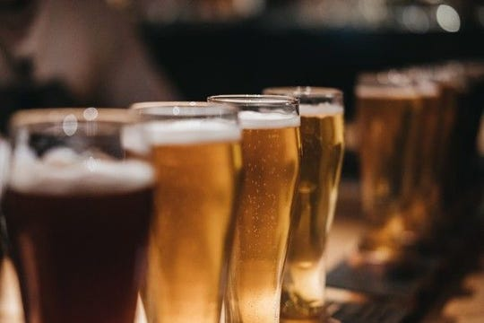 Beer in glasses lined up on bar.