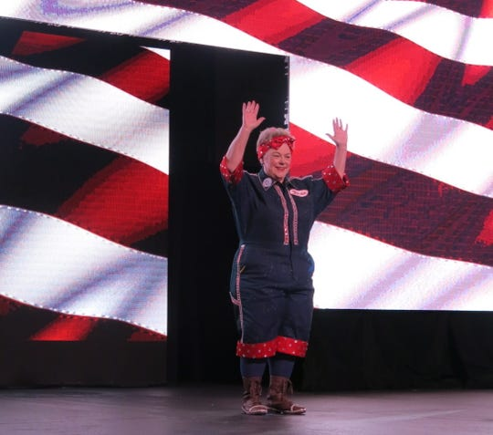 """Krewe des Ambassadeurs-Minden Captain XIX Mahala Hutto is introduced at the Grand Ball """"Putting on the Red, White and Blue."""" She played the part of  the World War II icon """"Rosy the Riveter."""""""
