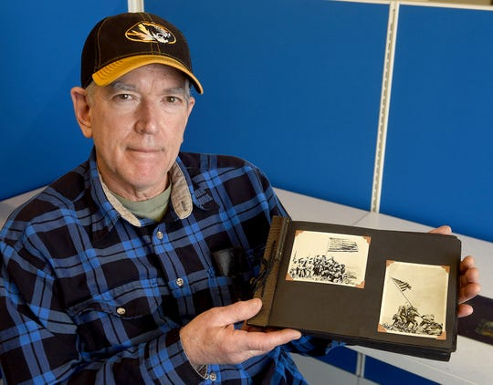 Kenny Bassett displays a photo album he bought at a garage sale about five years ago that contains 52 photos by Joe Rosenthal, Associated Press photographer. Roenthal received the Pulitzer Prize for his iconic World War II photograph of American soldiers raising of the American flag on Iwo Jima.