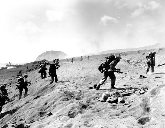 U.S. Fourth Division Marines move in from the beach Feb. 19, 1945 on Iwo Jima. A dead Marine lies at right in the foreground. Mt. Suribachi, in the background, was turned into a beehive of guns by Japanese troops.
