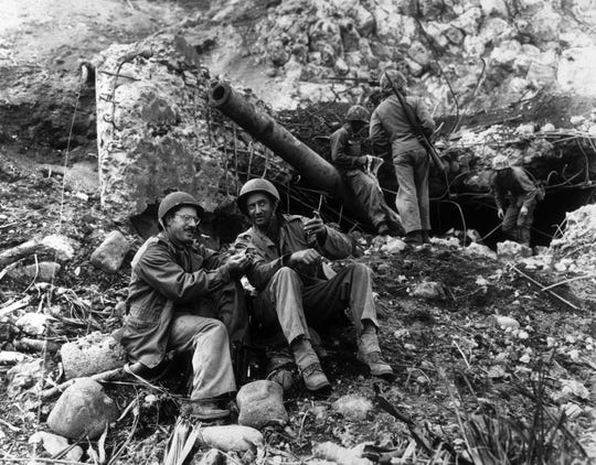 Associated Press photographer Joe Rosenthal left, takes time out to rest March 2, 1945, with Bob Campbell, right, a Marine from San Francisco, in front of a large Japanese gun knocked out by Marines at the base of Mount Suribachi on Iwo Jima.