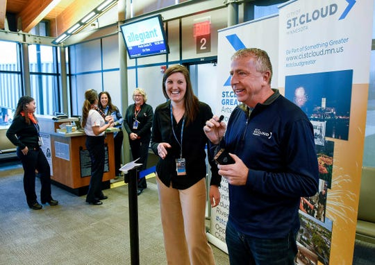 St. Cloud Mayor Dave Kleis and Michelle Whaley, public relations specialist for Allegiant, greet the first passengers to board the first flight to Punta Gorda, Florida in November 2017 at St. Cloud Regional Airport.