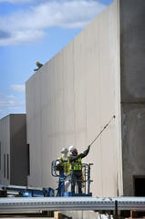 A painting crew applies a tan color to the exterior of the Wichita County Law Enforcement Center Monday.