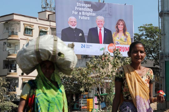 FILE - In this Feb. 18, 2020, file photo, Indian women walk past a hoarding showing Indian Prime Minister Narendra Modi, President Donald Trump and first lady Melania Trump to welcome them ahead of their visit to Ahmadabad, India. Trump is scheduled to visit the city during his Feb. 24-25 India trip. American dairy farmers, distillers and drug makers have been eager to break into India, the world's seventh-biggest economy but a tough-to-penetrate colossus of 1.3 billion people. Looks like they'll have to wait. Talks between the Trump administration and New Delhi, intended to forge at least a modest deal in time for President Donald Trump's visit there, appear to have fizzled. Barring some last-minute dramatics - always possible with the Trump White House - a U.S.-India trade pact is months away, if not longer. For now, the failure to reach an accord may reflect not so much the differences between Trump and Prime Minister Narendra Modi as the similarities.