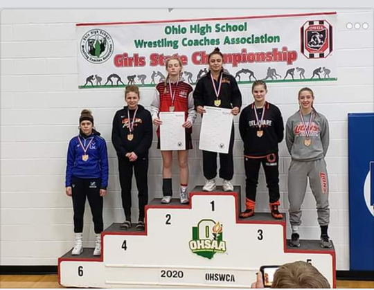 New Lex's Leilah Castro (above the No. 1) stands atop the podium after winning the 121-pound division on Sunday at the high school girls state wrestling championships.