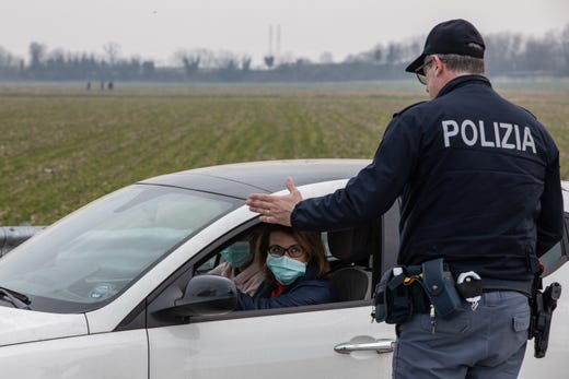An Italian National Police officer talks to a driver in a car, wearing a respiratory mask, on Feb. 23, 2020 in Casalpusterlengo, Italy. Casalpusterlengo is one of ten small towns placed under lockdown.