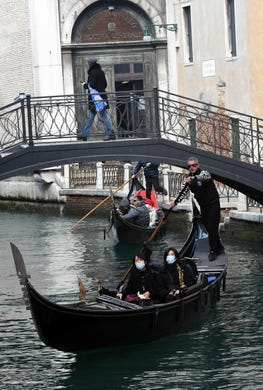 Asian tourists wearing protective masks take a ride on a gondola in Venice after the carnival was canceled due to a coronavirus outbreak in Italy, on Feb. 24, 2020.