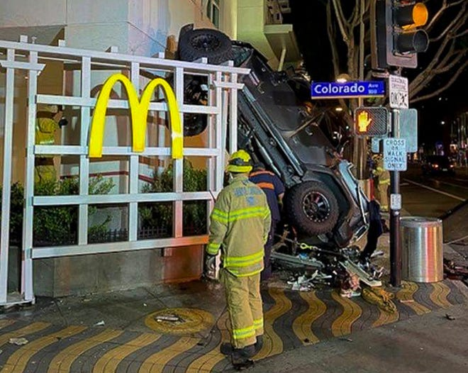 A photo released by the Santa Monica Fire Department shows a vehicle that plunged into the sidewalk after a man drove his Jeep off the sixth floor of a nearby parking garage. Responding officers found the destroyed vehicle up against a McDonald's restaurant across the street. (Santa Monica Fire Department via AP)