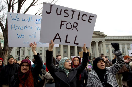 In this Jan. 29, 2017 file photo, demonstrators carrying signs chant as they protest outside of the White House in Washington during a demonstration to denounce President Donald Trump's executive order banning travel to the U.S. by citizens of Iraq, Syria, Iran, Sudan, Libya, Somalia and Yemen.