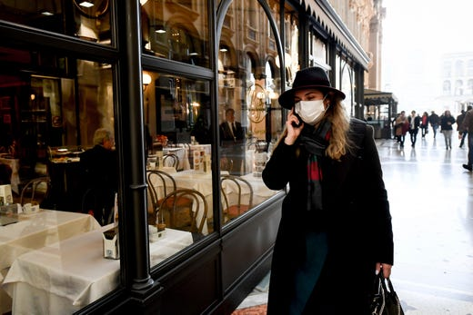 A woman wearing a sanitary mask talks on the phone as she walks in the Vittorio Emanuele Gallery shopping arcade, in downtown Milan, Italy, Feb. 24, 2020. A