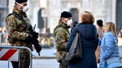 Italian soldiers wearing sanitary masks patrol Duomo square in downtown Milan, Italy, Monday, Feb. 24, 2020.