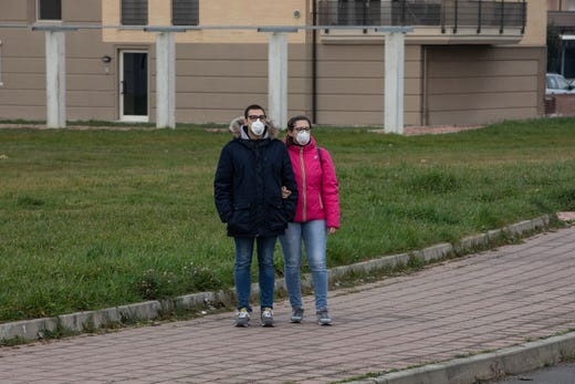 A couple, wearing respiratory masks, stands on a sidewalk  in Casalpusterlengo, Italy on  February 23, 2020.