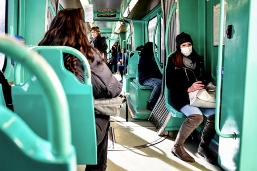 A woman wearing a sanitary mask sits in a streetcar in Milan, Italy, Feb. 24, 2020.