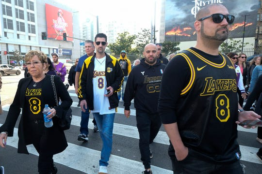 Fans walk to the Staples Center to attend a public memorial for former Los Angeles Lakers star Kobe Bryant and his daughter, Gianna, in Los Angeles, Feb. 24, 2020.