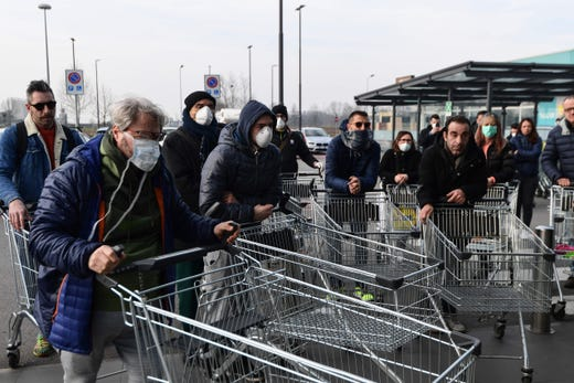 Residents wait to be given access to shop in a supermarket in small groups of forty people on Feb. 23, 2020 in the small Italian town of Casalpusterlengo, under the shadow of a new coronavirus outbreak, as Italy took drastic containment steps as worldwide fears over the epidemic spiralled.