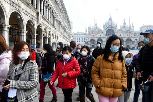 Tourists wearing protective facemasks visit the Piazza San Marco, in Venice, on Feb. 24, 2020 during the usual period of Carnival festivities.  The last two days of festivities have been cancelled due to an outbreak of the COVID-19 the novel coronavirus, in northern Italy. Italy reported on Feb. 24, 2020 its fourth death from the new coronavirus, an 84-year old man in the northern Lombardy region, as the number of people contracting the virus continued to mount.