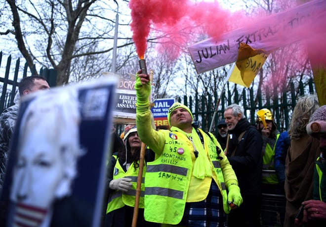 """A supporter of WikiLeaks founder Julian Assange, wearing a French themed """"yellow vest"""" or gilets jaunes, holds a flare as he calls for Assange's freedom outside Woolwich Crown Court on Feb. 24, 2020."""