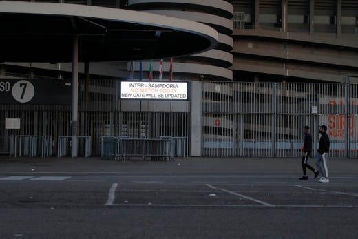 Two people walk by a notice outside San Siro stadium advising that the Serie A soccer match between Inter and Sampdoria is cancelled, in Milan, Italy, Feb. 23, 2020. In Lombardy, the hardest-hit region by the spread of the Coronavirus with 90 cases, schools and universities were ordered to stay closed in the coming days, and sporting events were canceled. Lombardy's ban on public events also extended to Masses in churches in the predominantly Roman Catholic nation.