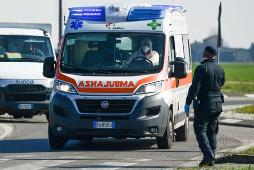 An ambulance drives past a police check-point near the small town of Castiglione d'Adda, southeast of Milan, on Feb. 24, 2020.