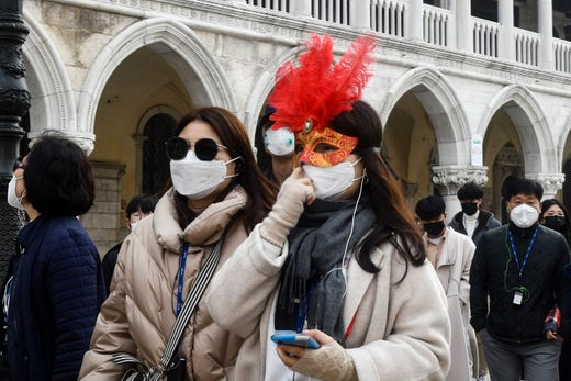 Tourists wearing protective facemasks and a Carnival mask visit the Piazza San Marco, in Venice, on Feb. 24, 2020 during the usual period of the Carnival festivities.
