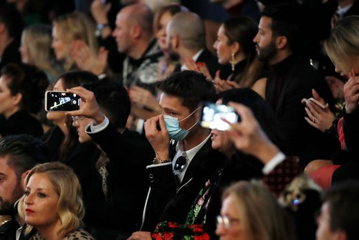 A man wearing a sanitary mask takes photos during the Dolce & Gabbana women's Fall Winter 2020-21 show, in Milan, Italy, Feb. 23, 2020.