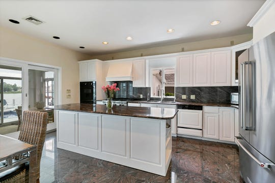 The kitchen features amazing floors, counter and granite stone center island.