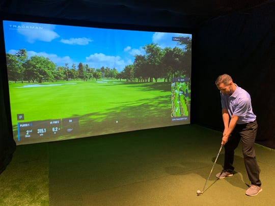 James Fiore, co-owner of Swing Loose Indoor Golf at Bell Works in Holmdel, gets ready to swing,