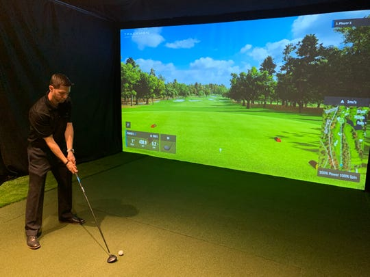 Peter Myers, co-owner of Swing Loose Indoor Golf at Bell Works in Holmdel, plays on a golf simulator, which uses real golf balls and clubs.