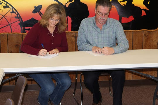 The Taylor County Expo Center's Rochelle Johnson and Taylor Telecom's Steve Singletary sign Monday a 10-year agreement for sponsorship rights to the Expo Center's multi-purpose arena.