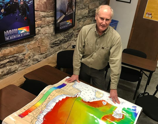 In search of the perfect shipwreck site:  Jonathan Eddy, owner of Waterfront Diving Center in Burlington displays a map of Burlington Bay showing relative water depths (red is most shallow) on Feb. 25, 2020. The map, viewed from the north here, was created by Tom Manley, an assistant professor of geology at Middlebury College, using multibeam sonar.