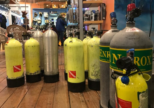 """Compressed air tanks fill one corner of the Waterfront Diving Center in Burlington on Feb. 25, 2020. The center's owner, Jonathan Eddy, is one of many experts advocating for the safe sinking (""""reefing"""") of the ferry boat Adirondack in Burlington Bay."""