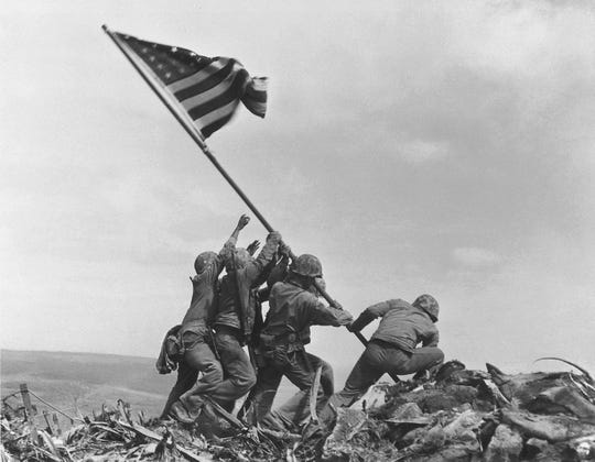 In this Feb 23, 1945 file photo, U.S. Marines of the 28th Regiment, 5th Division, raise the American flag atop Mt. Suribachi, Iwo Jima, Japan. This was the second flag ordered to be raised on the island that day and the most famous photo. The Marines first raised a smaller flag a few hours earlier. Marines fighting on the island cheered when they first saw the flag.