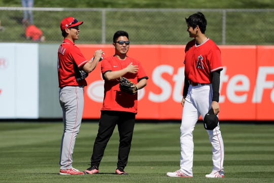 Cincinnati Reds' Shogo Akiyama, left, talks with Los Angeles Angels' Shohei Ohtani before a spring training baseball game, Tuesday, Feb. 25, 2020, in Tempe, Ariz.