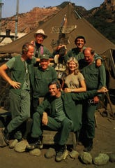 """1983: The """"M*A*S*H"""" cast for the 11th and final season (1982-83) which ended with a 2-1/2 hour """"Goodbye, Farewell, and Amen"""" special on Feb. 28, 1983. Seated in front: Alan Alda. Second row: (L-R) Mike Farrell, Harry Morgan, Loretta Swit, David Ogden Stiers. Back row: L-R William Christopher, Jamie Farr."""