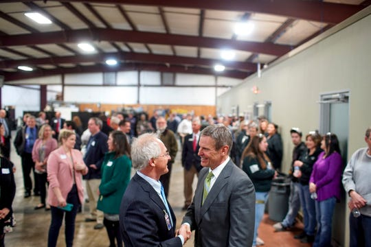 Gov. Bill Lee shakes the hand of AES president John Sonday on Monday.