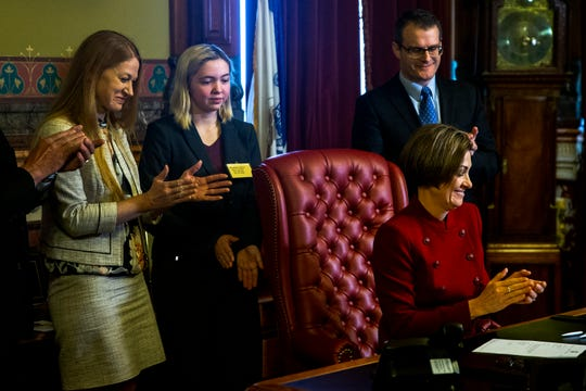 Governor Kim Reynolds signs S.F. 2164, a bill to help schools with transportation funding, on Tuesday, Feb. 25, 2020, in her formal office at the Iowa State Capitol in Des Moines.