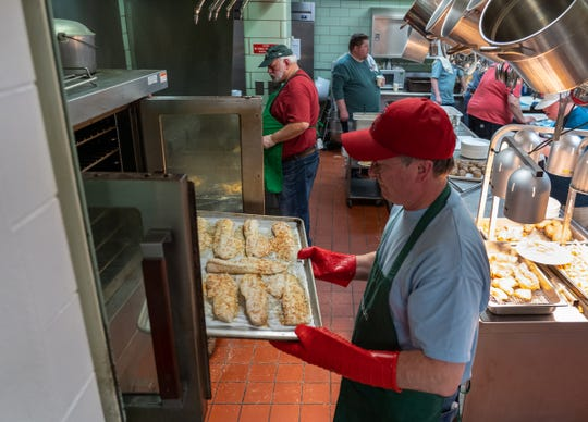 Craig Sleeman pulls baked cod out of the oven during a fish fry at The United Methodist Church in Royal Oak. The fish fry is now in its 24th year.