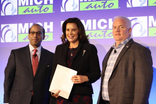 Michigan Gov. Gretchen Whitmer, center, stands at the MICHauto Summit holding a signed executive order creating a council on future mobility and electrification, and establishing the Michigan Office of Future Mobility on Feb. 25, 2020.