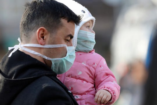 A man holds a baby while walking by the entrance of Zekai Tahir Burak Hospital where 17 passengers of a Turkish Airlines flight from Tehran, suspected of having coronavirus, were to be quarantined, in Ankara, Turkey, Tuesday, Feb. 25, 2020.
