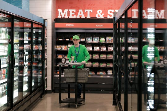 A worker pushes a cart inside an Amazon Go Grocery store.