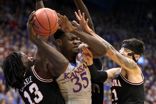 Kansas center Udoka Azubuike (35) rebounds between Oklahoma State guards Isaac Likekele (13) and Lindy Waters III (21) during the first half.
