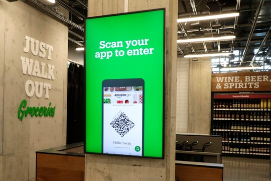 A sign tells shoppers how to check in when they enter an Amazon Go Grocery store.