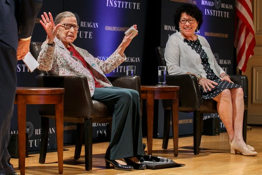 Supreme Court Justice Ruth Bader Ginsburg, left, holds up her hands as she and Supreme Court Justice Sonia Sotomayor arrive to applause for a panel discussion celebrating Sandra Day O'Connor, the first woman to be a Supreme Court Justice, Wednesday Sept. 25, 2019, at the Library of Congress in Washington.