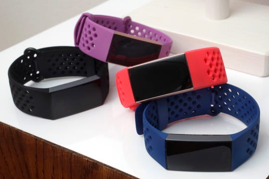 FILE - In this Aug. 16, 2018, file photo, the new Fitbit Charge 3 fitness trackers with sport bands are displayed in New York.
