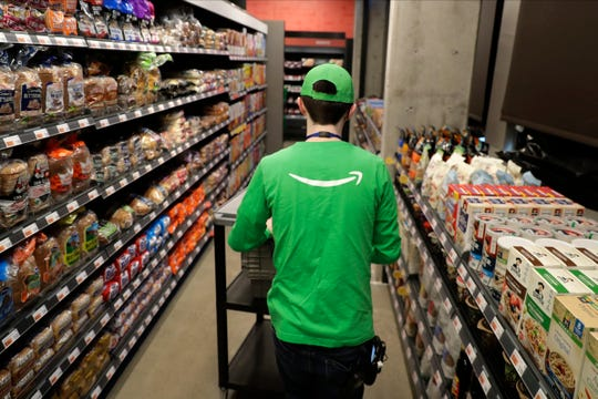 A worker pushes a cart inside an Amazon Go Grocery store set to open soon in Seattle's Capitol Hill neighborhood.