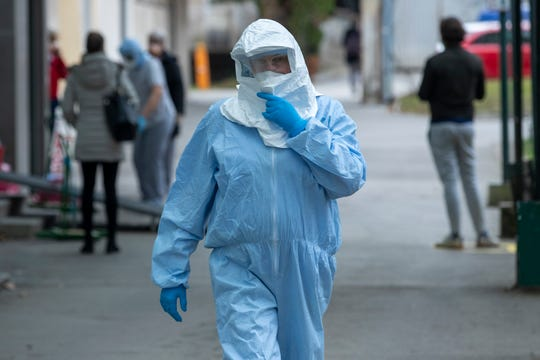 A health worker wears protective suit at the infectious disease clinic in Zagreb, Croatia, where the first coronavirus case in Croatia is hospitalized, Tuesday, Feb. 25, 2020.
