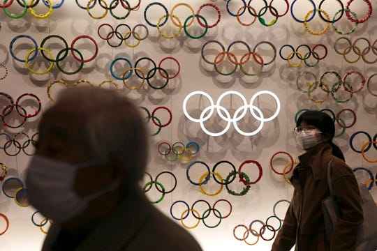 Two people wear masks as they visit the newly opened Japan Olympic Museum located near the New National Stadium.