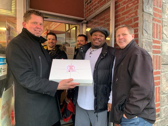 Ken Morgulec shows off a box of paczki as he poses with Ronald Wells and Eric Gunderson outside New Palace Bakery in Hamtramck after waiting over two hours.