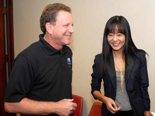 """FILE - In this Dec. 1, 2006 file photo Honolulu Marathon president and CEO Dr. James Barahal, left, shares a laugh with Yunjin Kim, right, of ABC's """"Lost"""" during a Honolulu Marathon news conference in Honolulu."""
