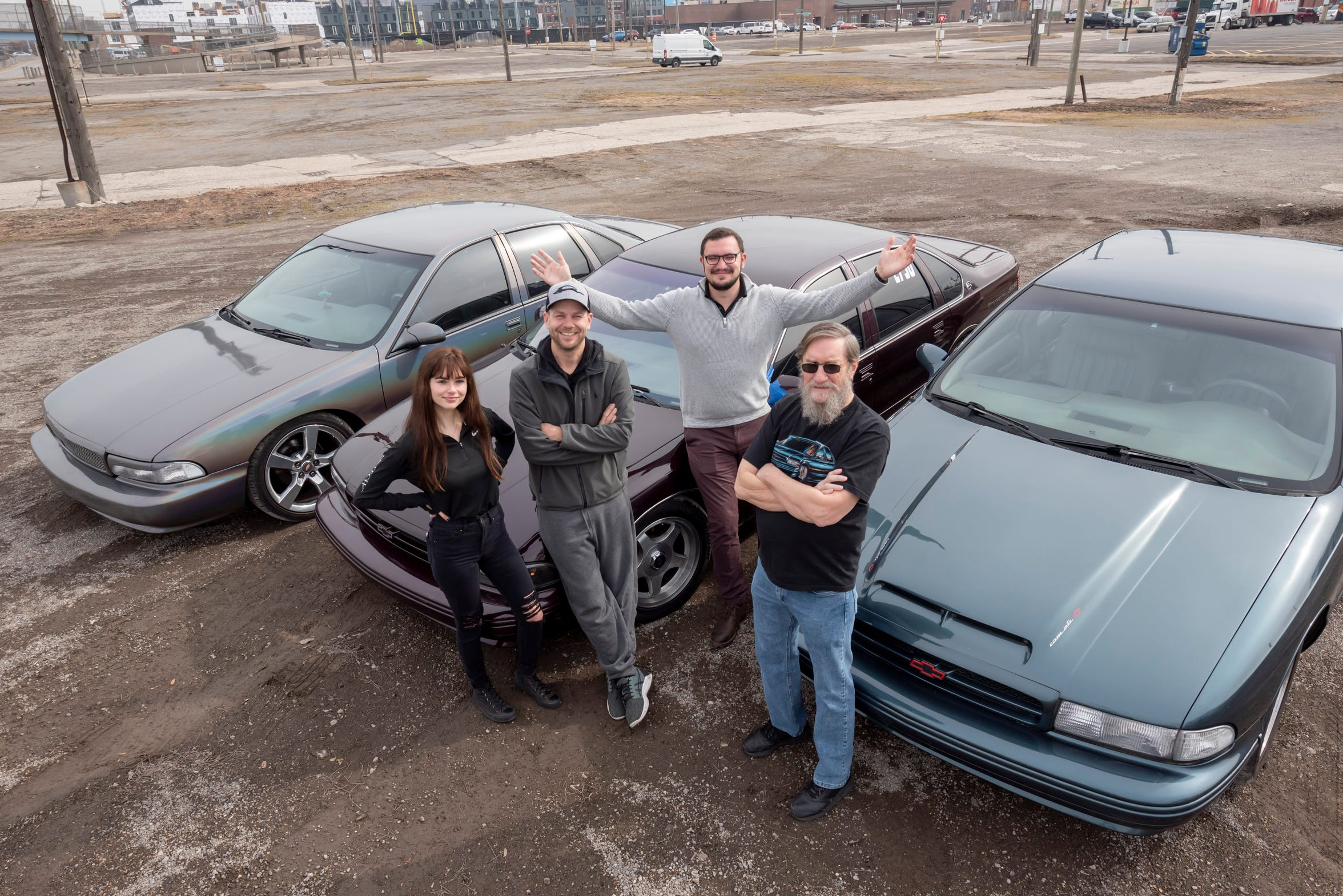 Hunter Gersch, from left, her father Daniel Gersch, Glenn Waineo, and Mitchell Bergslien, stand in front of examples of the 1996 Chevy Impala SS.